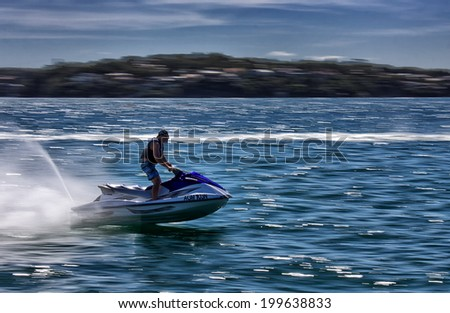 BUNDEENA,AUSTRALIA - SEPTEMBER 29, 2013: A man rides a jet ski at speed. Jetskis are controversial in the area, with public meetings held regarding reckless behaviour by riders.