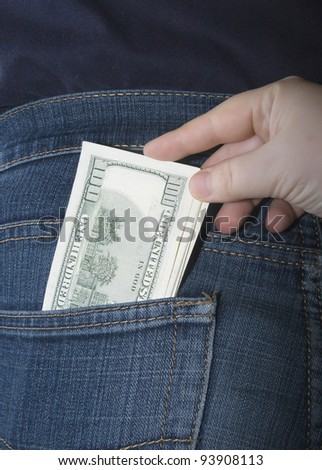 Bundle of dollars in a jeans rear pocket and a hand pulling them out