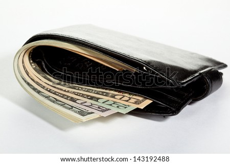 Bundle of dollars in leather wallet on neutral background