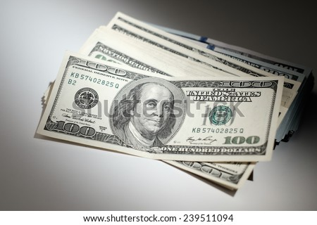 Bundle of dollars on a white table. 100 dollar bills - stock photo