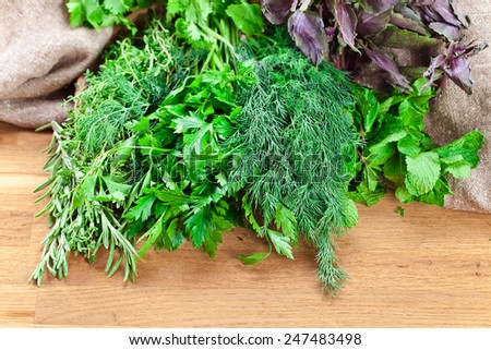 Bundle of fresh kitchen herbs on wooden table