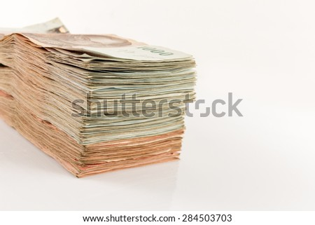 Bundle of money stacked on a white background.
