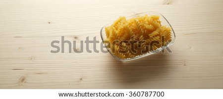 Bundle of raw uncooked Italian pasta macaroni lying on a textured wooden surface with shallow dof and with space for text  - banner / header edition - stock photo