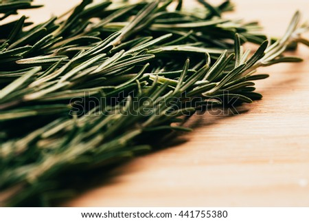 bundle of sprigs of rosemary on a wooden light background.