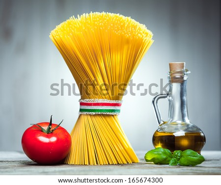 Bundle of uncooked dried Italian spaghetti tied with a ribbon in the colours of the national flag - red, white and green - with a decanter of olive oil, basil and a tomato - stock photo