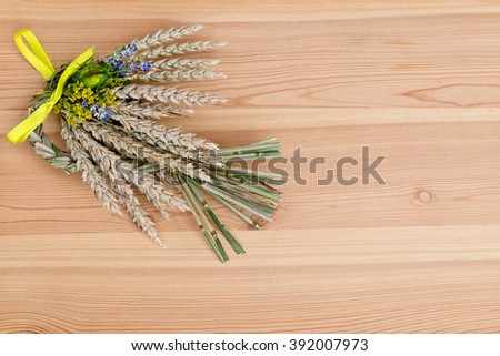 bundle of wheat with flower and band on the wooden desk