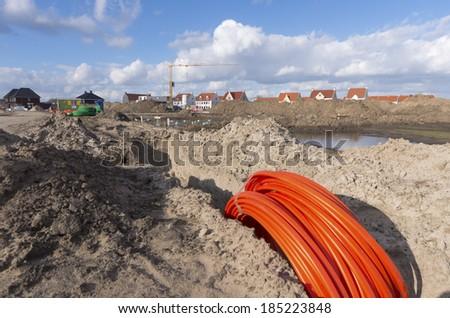 bundle orange fiber cable on a construction site - stock photo