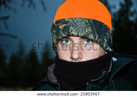 Bundled up teen boy on an early morning deer hunt, dressed for the cold weather. - stock photo
