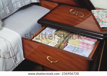 Bundles of banknotes in bedside table filled with Ukrainian cash - stock photo