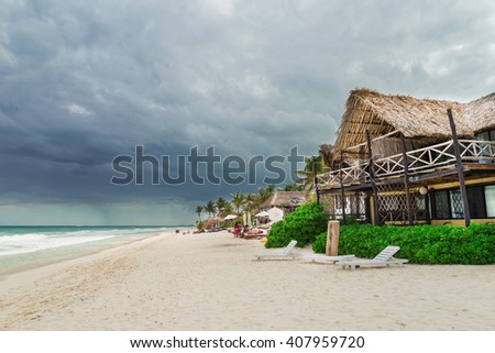 Bungalow hotel on the beach. Beautiful beach. Storm sky over the sea. Tulum, Mexico, Carribean - stock photo
