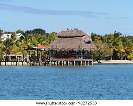 Bungalow on stilts with thatched roof over water and tropical beach in background - stock photo