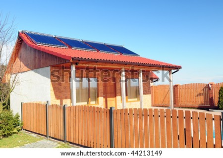 Bungalow with solar panels on the roof and fragment of wooden fence. - stock photo