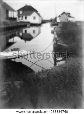 Bungalows at the water's edge in Oceanside, a small passageway of water flanked by houses and docks, Long Island, New York, photograph by Gertrude Kasebier, 1905. - stock photo