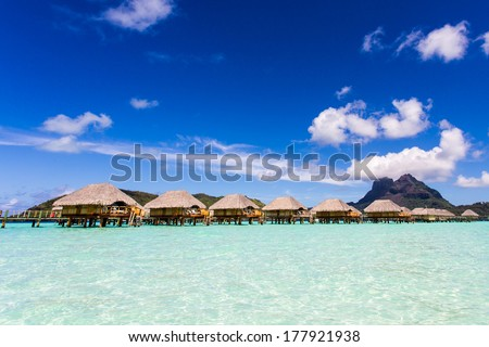 Bungalows on stilts in the turquoise water on the background of the island of Bora Bora - stock photo