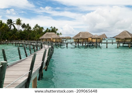 Bungalows over water in tropical dream destinations - stock photo