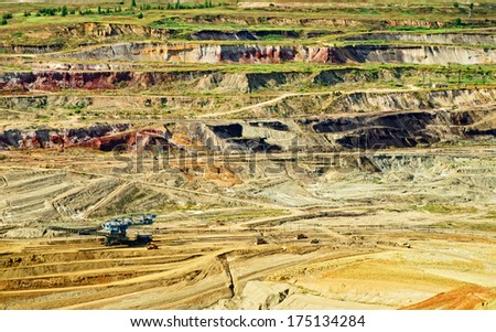 Bunk wall surface mine with exposed colored minerals and brown coal, at the bottom of the pit mining equipment, view from above - stock photo