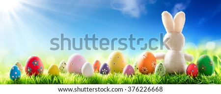 Bunny With Decorated Eggs On Sunny Meadow - Spring And Easter Background - stock photo