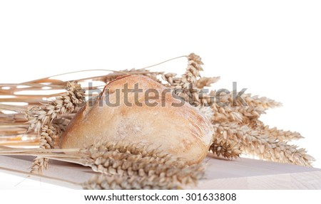 Buns and Wheat on wooden board over white background - stock photo