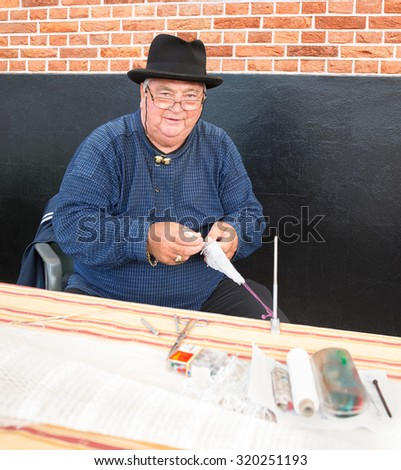 BUNSCHOTEN-SPAKENBURG, THE NETHERLANDS - SEPT 5, 2015: Unidentified fisherman demonstrates how to weave a fishing net during the annual fishery day, held in the streets of the town