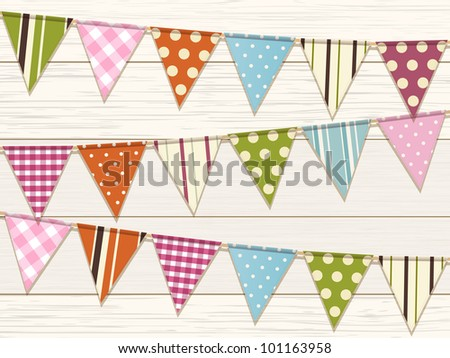 Bunting with bright patterns on a white wood background - stock photo