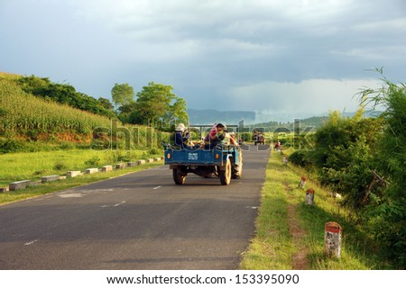 BUON ME THUOT, VIET NAM- SEPT 02: Group of farmer moving by farm tractor on country road at Vietnamese countryside, lifestyle of poor ethnic people, transport by farm truck, Vietnam, Sept 02, 2013