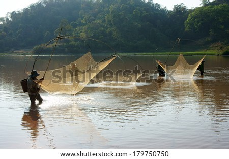 BUON ME THUOT, VIETNAM- FEB 7: People catch fish on ditch, fisherman lifting net from water, lift net is primitive traditional tool, include net, rod, four corner hang up 4 frame, Vietnam, Feb 7, 2014