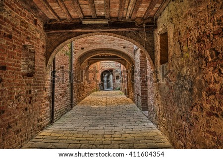Buonconvento, Siena, Tuscany, Italy : the picturesque covered street Via Oscura, a narrow dark alley in the medieval town