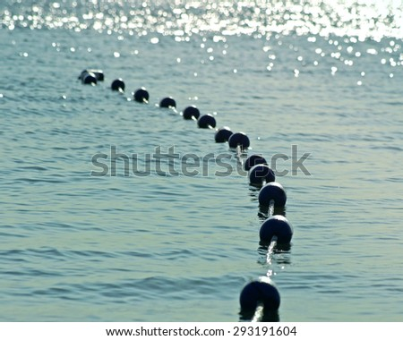 Buoys strung together on beautiful blue sparkling waters in early morning.  Safety buoys to create safe swimming area for swimmers