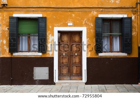 Burano island near Venice, Italy - House with orange-brown facade, wooden door and two symmetrical windows.