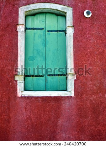 Burano island, Venice. Closed window with green shutter on red wall.  Colorful houses island and landmark of Veneto region, Italy - stock photo