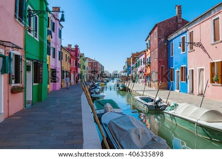 Burano island water canal, colorful houses and boats. Beautiful touristic destination near Venice, full of small shops and cafes. Burano island, Venice, Italy.  - stock photo
