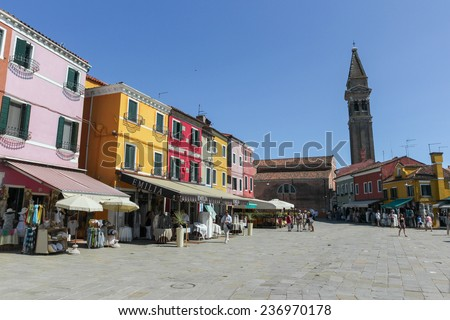 BURANO, ITALY - JULY 16, 2012:  Central square between colorful houses on the famous island Burano, Venice. Venice and the Venetian lagoon are on the UNESCO World Heritage List. july 16, 2012 - stock photo