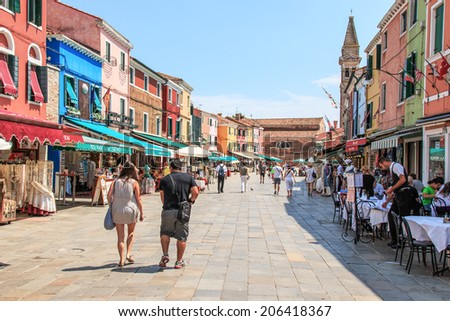 Burano, Italy - June 28, 2014:  Tourists and locals are enjoying a sunny day in June and are having lunch in a street restaurant in Burano.