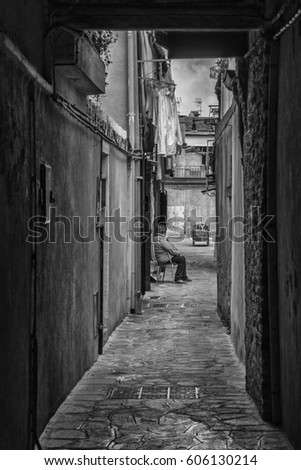 Burano, Veneto, Italy - March 6, 2017 : A local woman sitting outside in a small alley in Burano