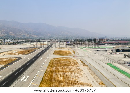 BURBANK, USA - MAY 27, 2015: Aerial view of the airport with runways, a hangar and parked airplanes.