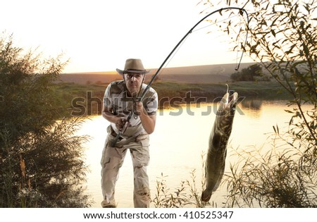 Burbot. Man fishing  in the river at sunset