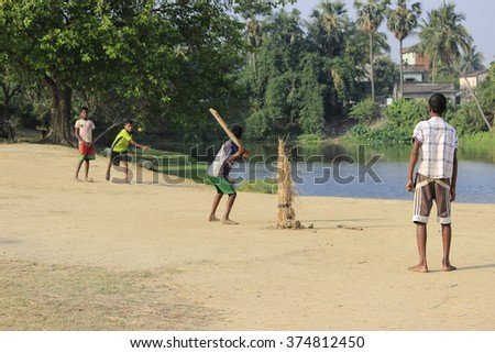 Burdwan, West Bengal, India on 29th April,2014 - Indian children are playing cricket beside a pond on 29th April. - stock photo