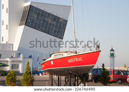 Burgas - August 28: A small red boat on the shore, a small lighthouse and building terminal of August 28, 2015 Bourgas, Bulgaria