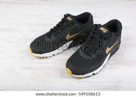 BURGAS, BULGARIA - DECEMBER 29, 2016: Nike Air MAX women's shoes - sneakers in black, on white wooden background. Nike is a global sports clothes and running shoes retailer.