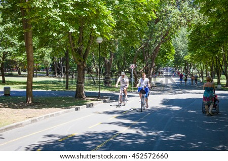 Burgas - July 9: Seaside Park - bicycle lane. Male and female cyclists puppy in the basket of the bicycle. Woman with stroller on July 9, 2016, Burgas, Bulgaria
