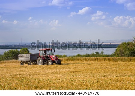 Burgas - July 4:Tractor trailer in a wheat field on the background of Lake Vaya, NHK and blue sky with white clouds on 4 July 2016, Bourgas, Bulgaria