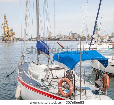 Burgas - June 9: Yachts, boats and lighthouse in the port amid cranes, warehouses and administrative and industrial buildings of June 9, 2015 Bourgas, Bulgaria