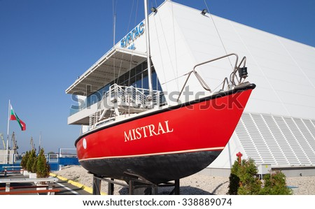 Burgas - October 25: A small red boat on the shore, and building Port of October 25, 2015 Bourgas, Bulgaria