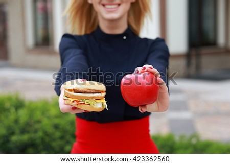 Burger and apple, closeup. Women's hands  holding healthy and unhealthy food. choice concept. - stock photo
