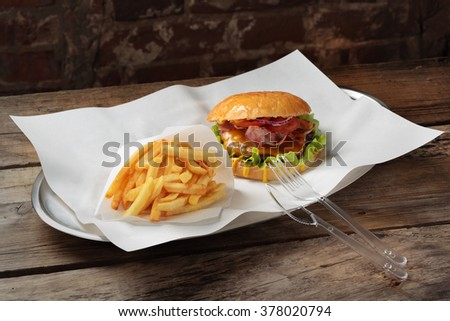 Burger and fries on a platter with white paper