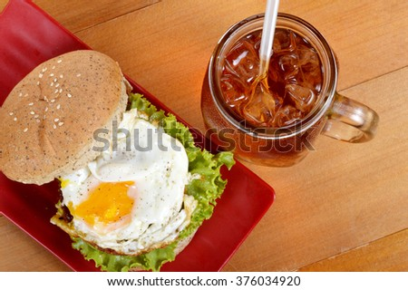 burger and iced tea on wooden board