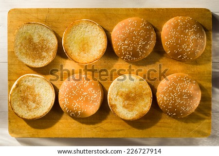 Burger buns with sesame seeds on a chopping board - stock photo