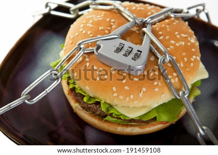 Burger, chained to the plate. Choose healthy food. - stock photo