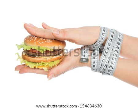 Burger cheeseburger in hands with measure tape isolated on white background. Healthy weight loss diet concept. - stock photo
