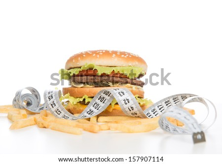 Burger cheeseburger meal with french fries chips tape measure on white background. Healthy weight loss diet concept. - stock photo